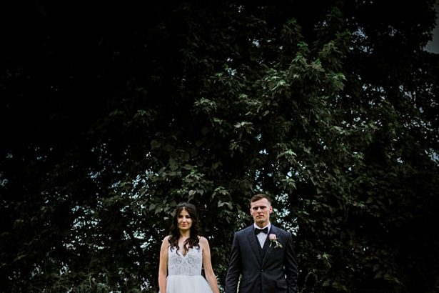Country Club Wedding epic wide shot of bride and groom in front of trees - Bluespark Photography