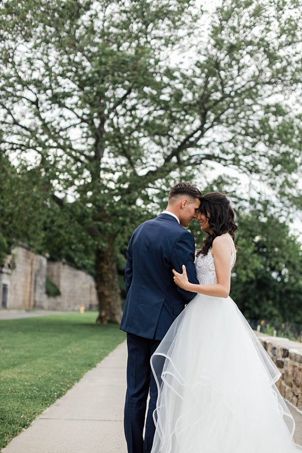 Country Club Wedding photo of bride and groom hugging outside - Bluespark Photography