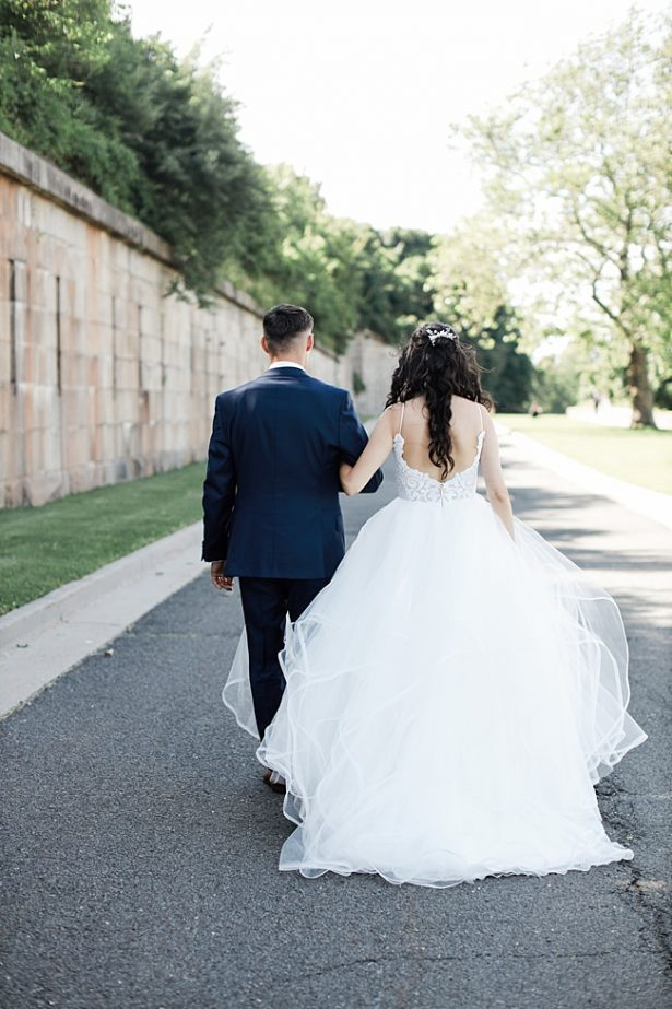 Country Club Wedding photo of bride and groom walking with bride in a ball gown - Bluespark Photography