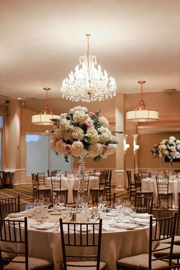 Country Club Wedding reception with tall floral centerpieces and chandelier - Bluespark Photography