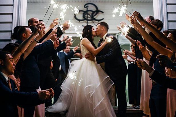 Country Club Wedding sparkler exit photo of bride and groom kissing - Bluespark Photography