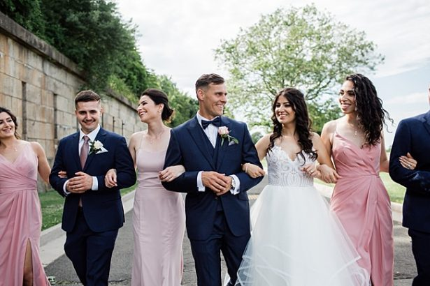 Country Club Wedding with blue and pink photo of bride and groom walking with bridal party - Bluespark Photography