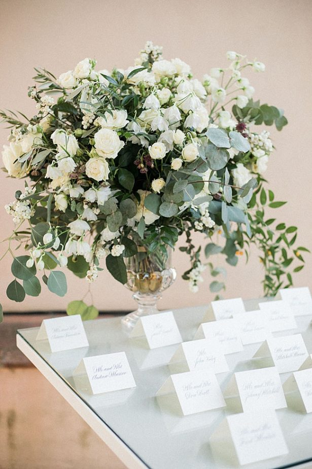 Elegant all white seating chart for wedding and white floral centerpiece with hanging greenery - Purewhite Photography
