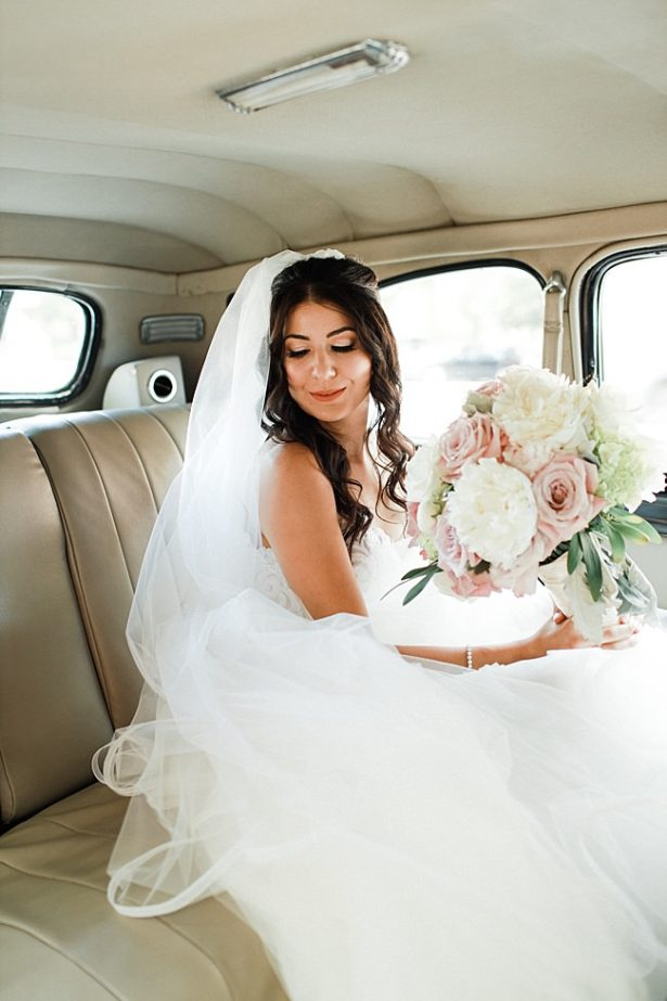 Glamorous bridal look with half up half down hair with loose curls a long veil and white and blush bride bouquet - Bluespark Photography