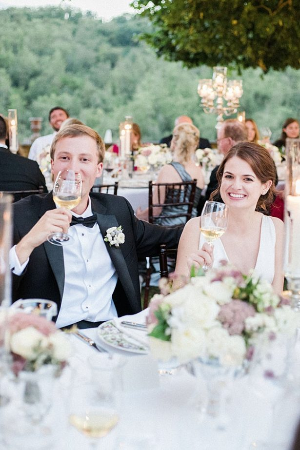 Outdoor wedding reception shot of bride and groom laughing during toasts - Purewhite Photography
