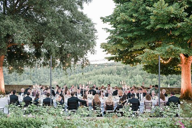 Perfect outdoor wedding reception in Tuscany with guests at tables under the trees and string lights - Purewhite Photography