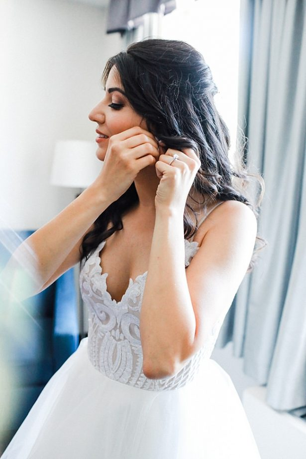Photo of bride getting ready putting in her earrings - Bluespark Photography