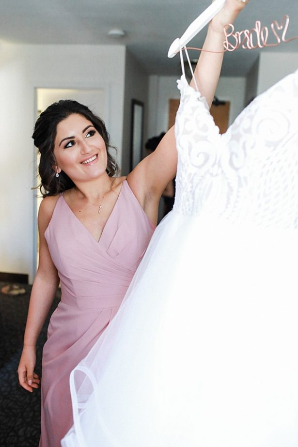 Photo of bridesmaid with brides dress for getting ready - Bluespark Photography