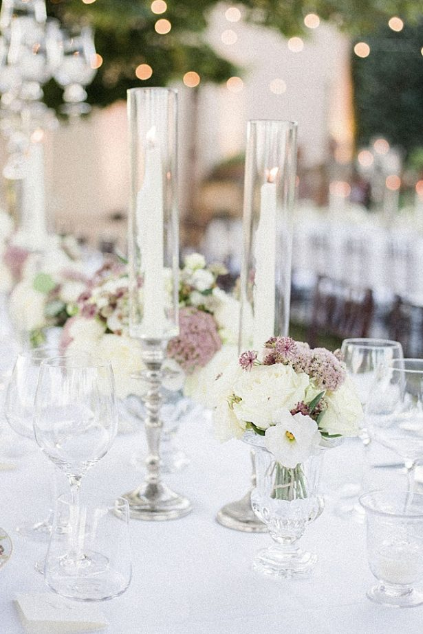 Romantic wedding reception table decor with tall glass candle votives and white and mauve floral centerpieces - Purewhite Photography