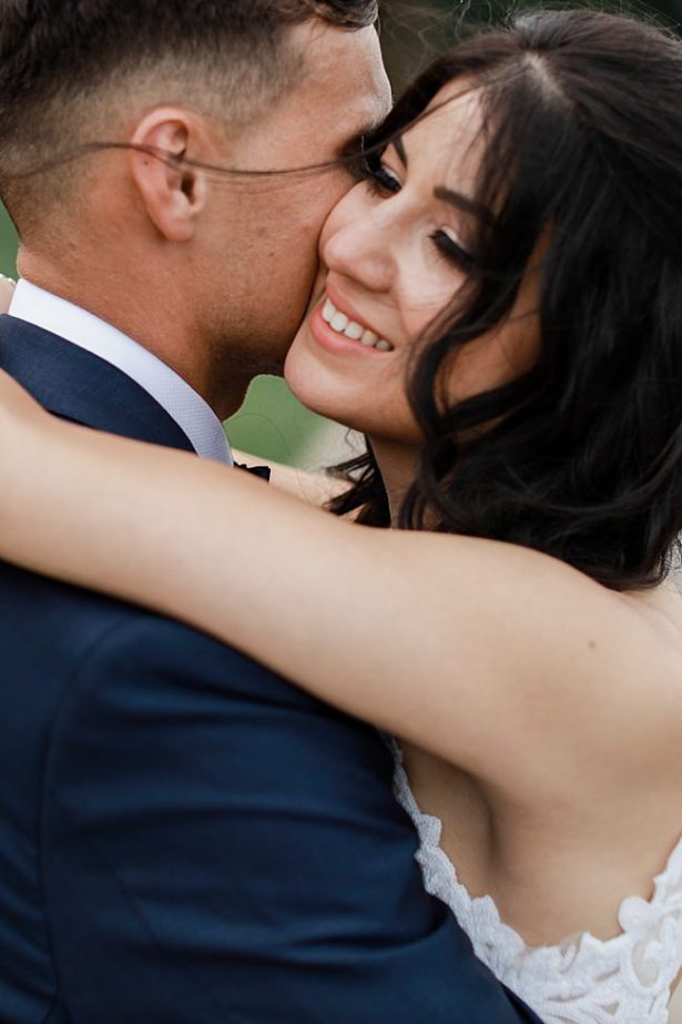 Romantic windswept photo of bride and groom hugging - Bluespark Photography