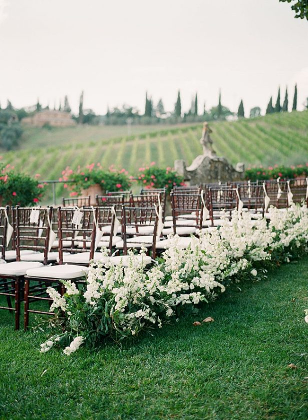 Tuscany Wedding ceremony decor with flowers down the aisle and the rolling hills behind it - Purewhite Photography