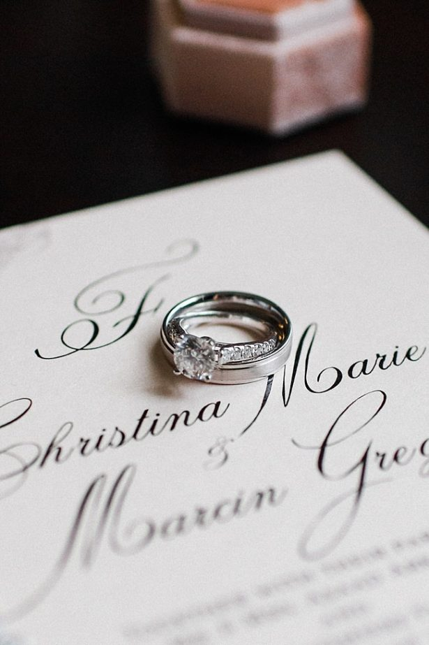 White gold wedding bands on white wedding invitations - Bluespark Photography