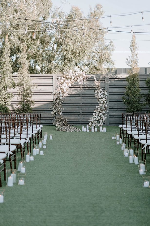 Unique shaped wedding-ceremony arbor with white flowers- Foolishly Rushing In Photography