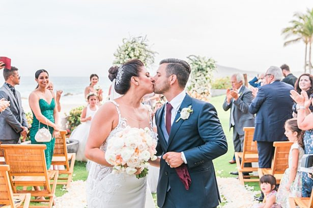 Beach wedding photo of bride and groom kissing down the aisle - Photography: JBJ Pictures