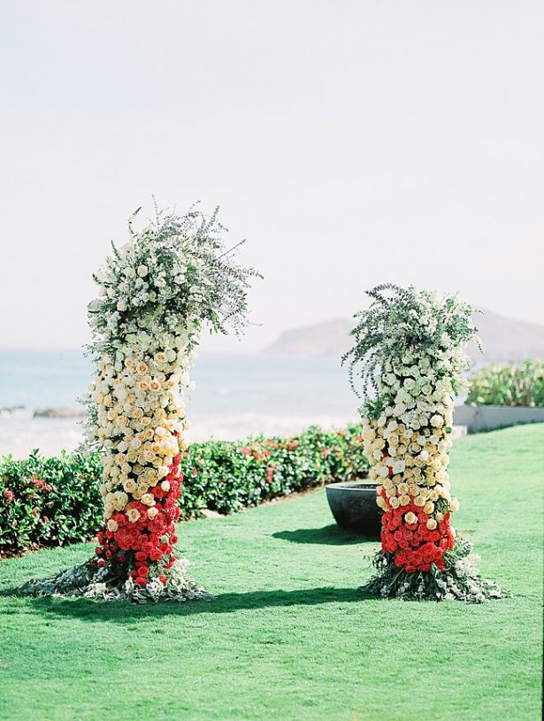 Cabo Destination Wedding ceremony flowers with peach and white flowers by the ocean - Photography: JBJ Pictures