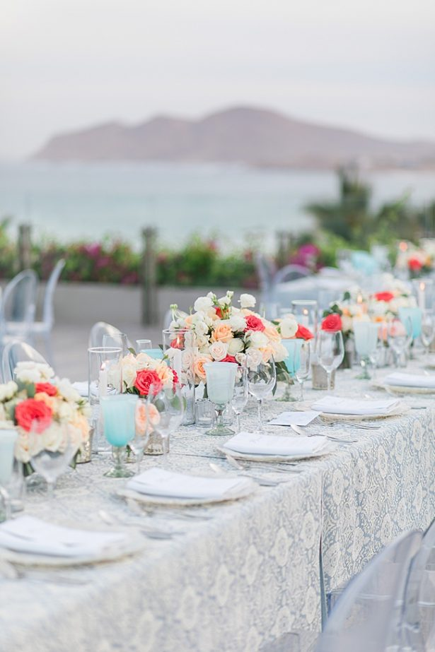 Cabo Destination Wedding overlooking the water with peach colored flower centerpieces - Photography: JBJ Pictures