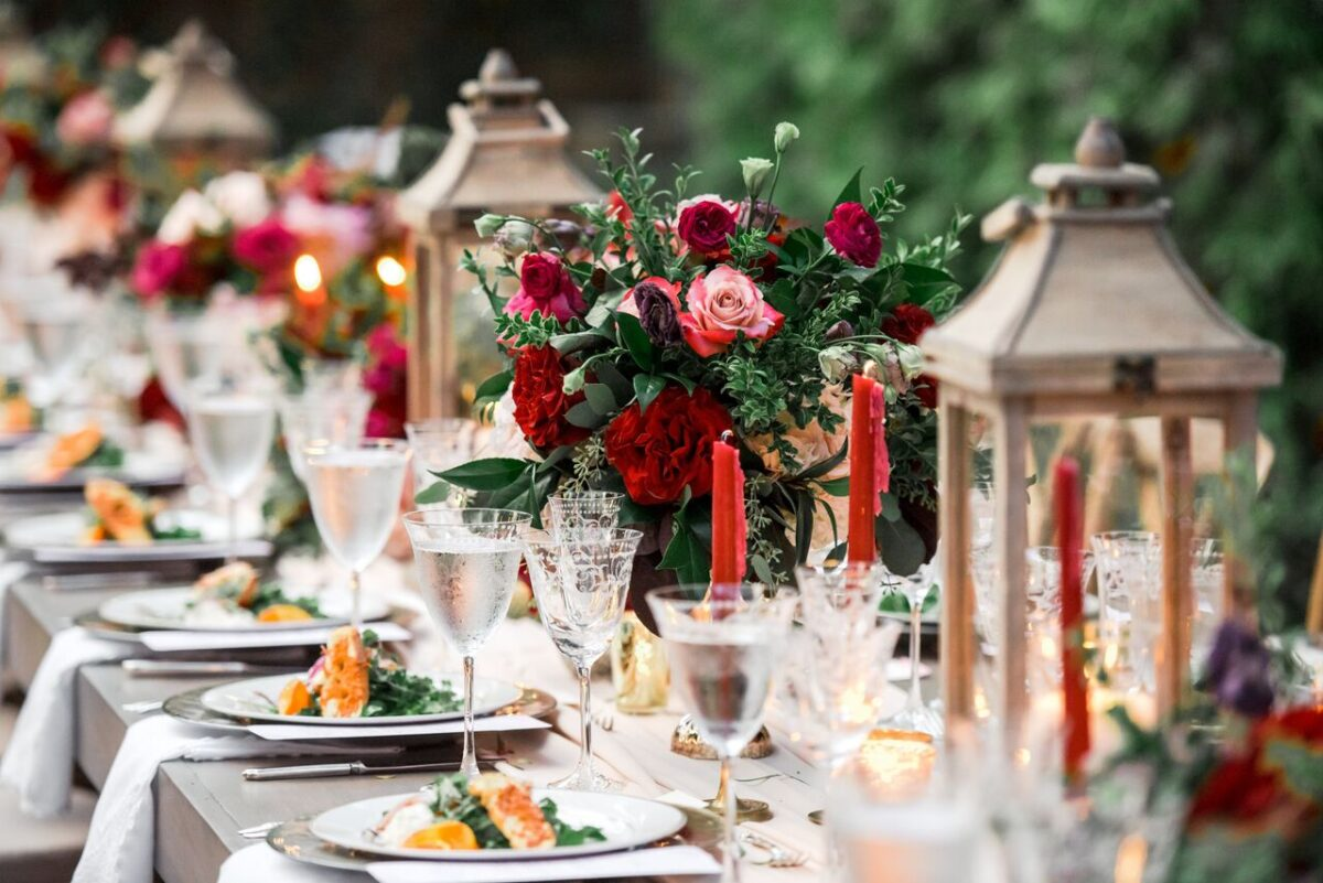 Long wedding tables with low wedding centerpieces and lanterns - Photography: Dmitry Shumanev