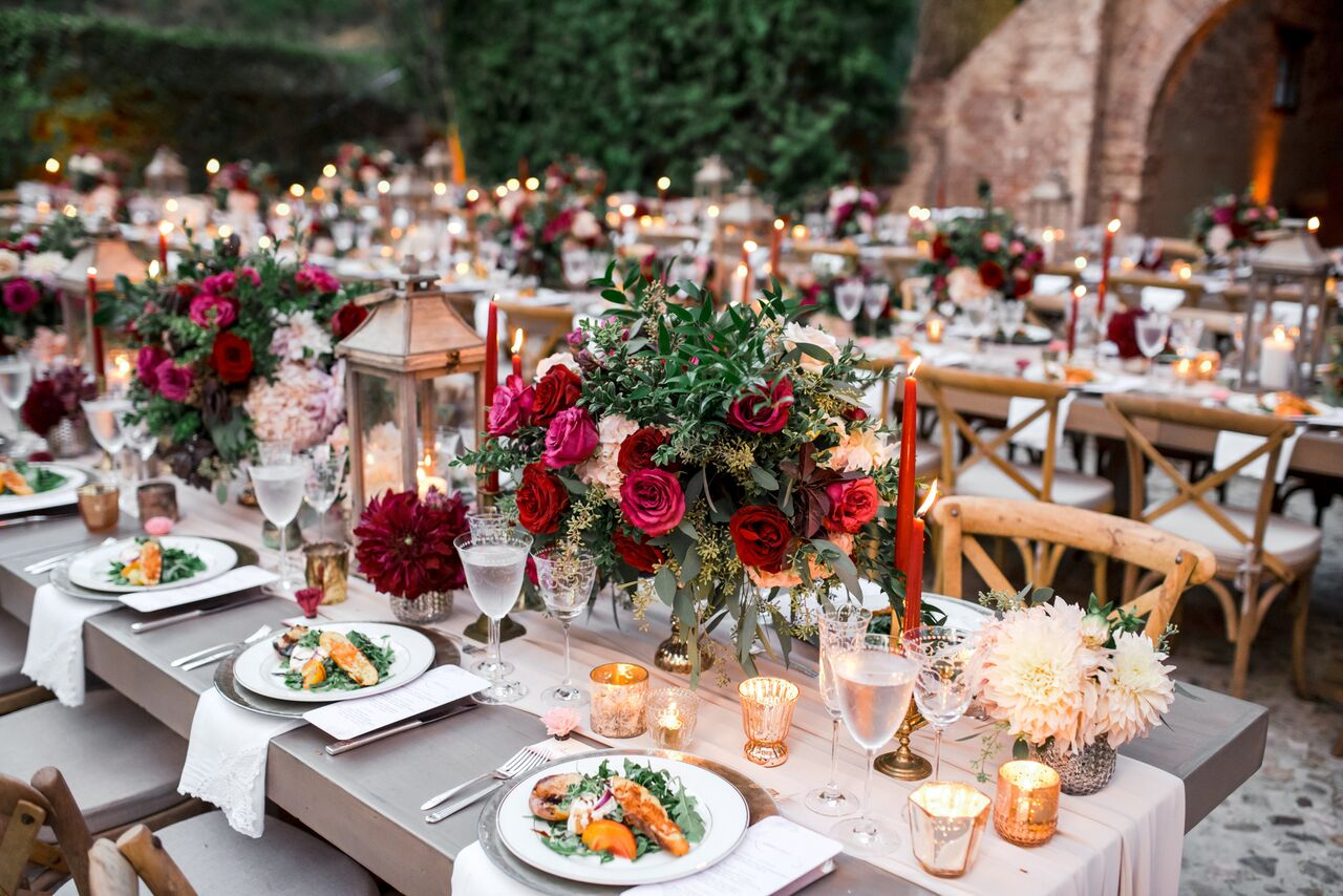 Long wedding tables with low wedding centerpieces and rustic chairs - Photography: Dmitry Shumanev
