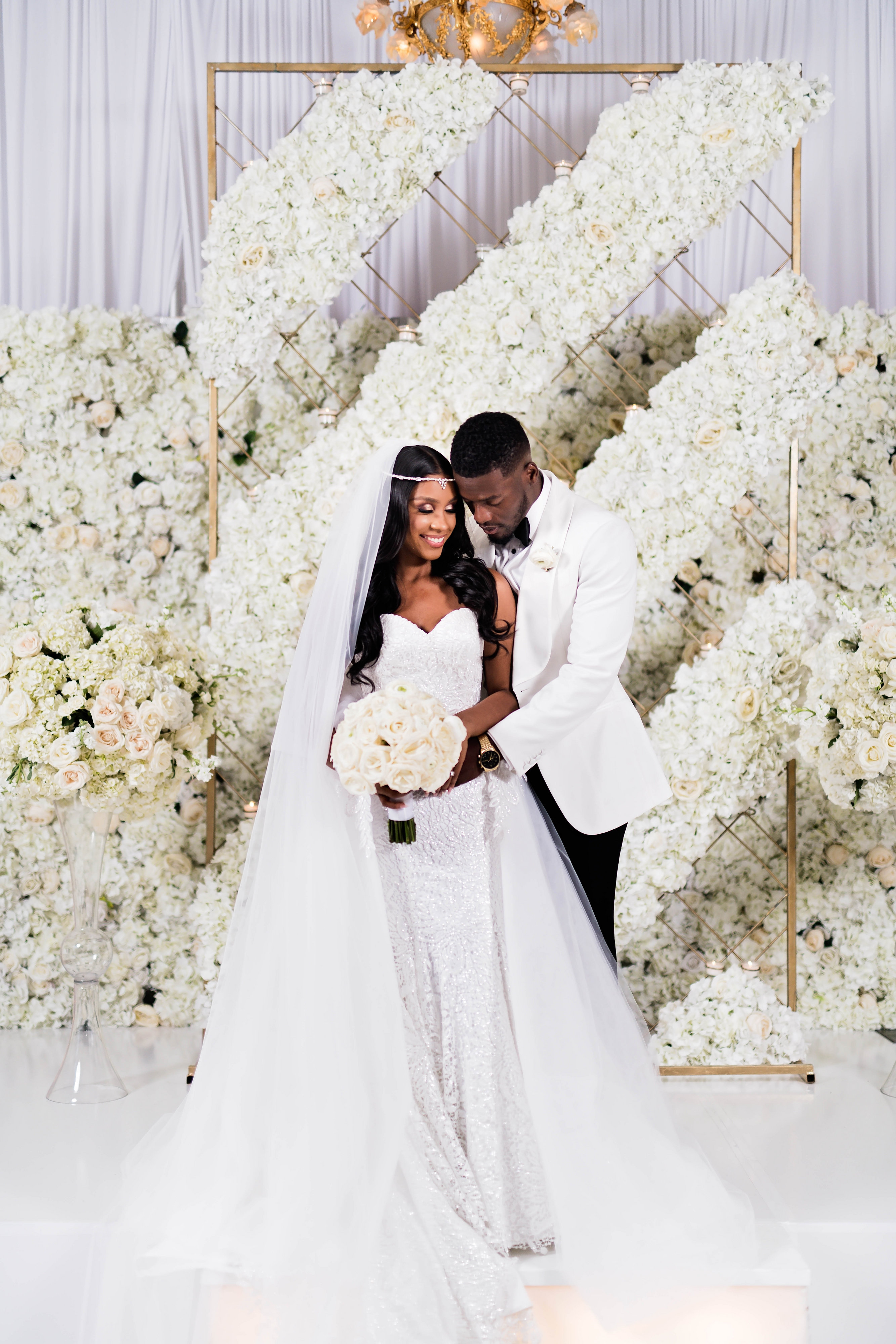 Luxury black bride and African American groom photo with floral wall - Photography: Pharris Photos