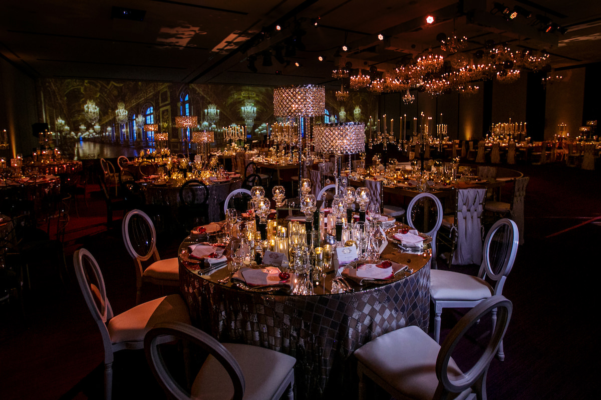 Glamorous indoor wedding reception with crystal chandeliers and candelabras - Nadia D Photo