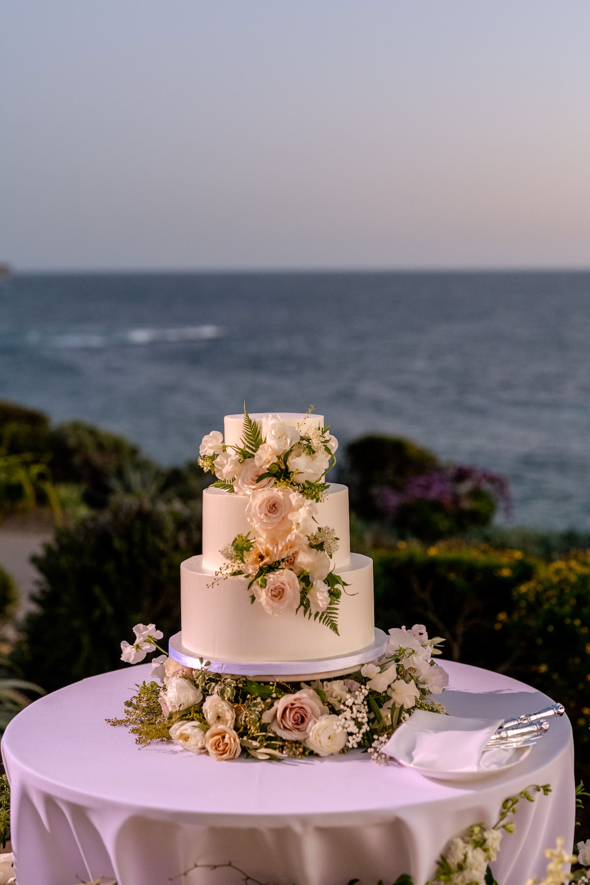 White wedding cake on table decorated with flowers - Holly Sigafoos Photo
