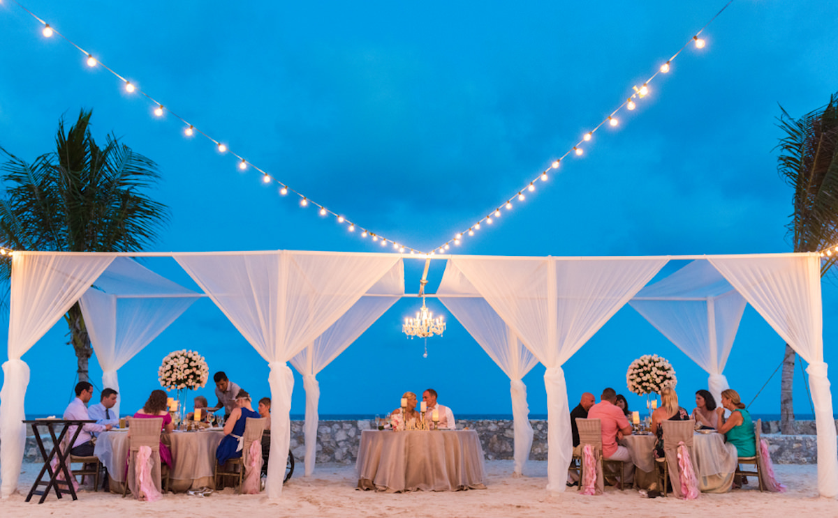 Beach wedding reception - white pergola with bulbs and chandelier